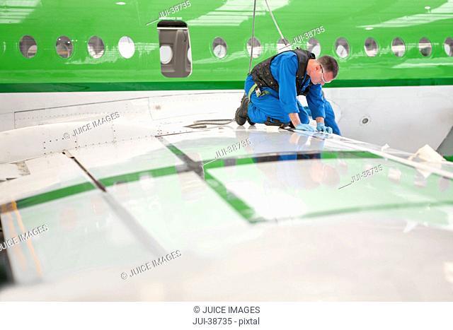 Engineer inspecting wing of passenger jet in hangar