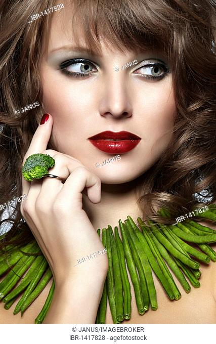 Portrait of a young woman with green beans as a necklace and a broccoli ring looking to one side, Jewelry