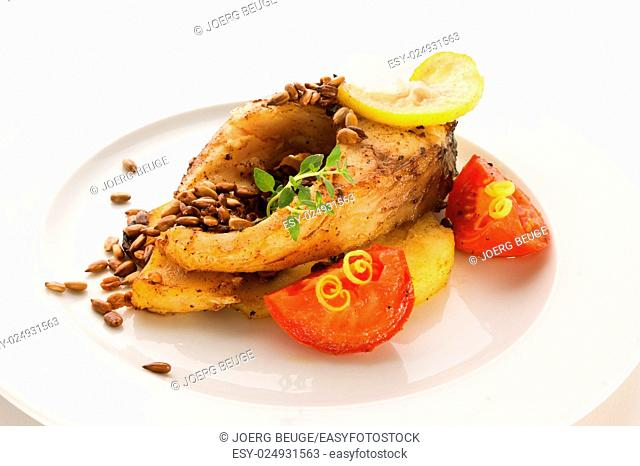 baked carp steak on potatoes, lentils, tomatoes and lemon zest on a white plate