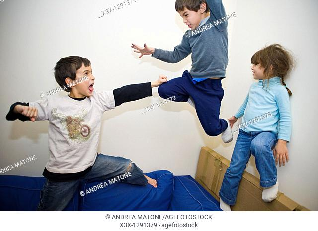 Male children play fighting on the sofa