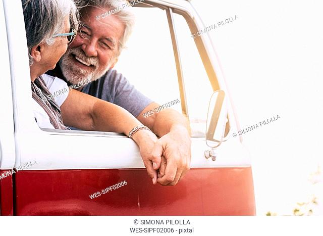 Senior couple traveling in a vintage van, looking at the sea