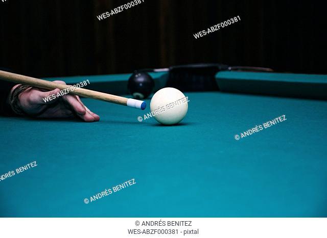 Hand of a man playing pool billard in a bar