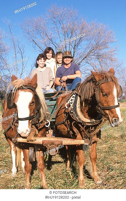 A family taking a ride on horses and wagon