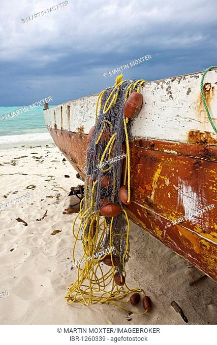Fishing boat, dhow, with nets and an approaching thunderstorm on the beach in Jambiani, Zanzibar, Tanzania, Africa