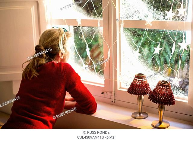 Mother looking out of window with Christmas decorations