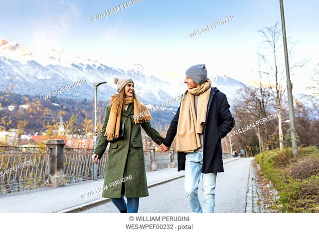 Austria, Innsbruck, happy young couple strolling together hand in hand at winter time