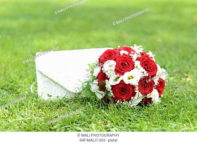 Brautstrauß und Handtasche auf dem Rasen