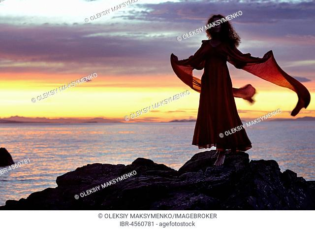 Young woman in long red dress, standing on rocks of an ocean shore in sunset