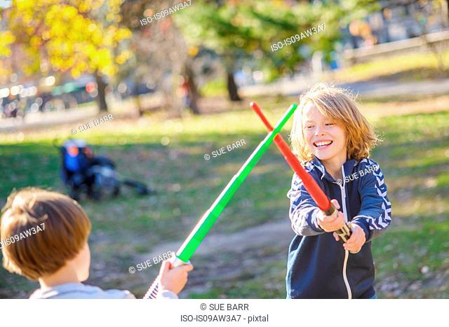 Two young brothers, play fighting with laser swords