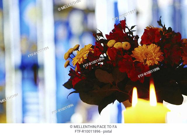 Bouquet of flowers and candles in a german church, Germany,Blue church windows