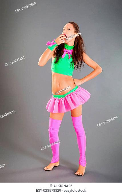 beautiful slim brown haired girl in fashionable green and pink dance costume stand barefoot closes mouth by hand posing in studio on grey background