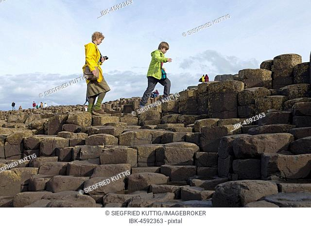 Tourists walk on the basalt columns, Giant's Causeway, Causeway Coast, County Antrim, Northern Ireland, Ireland, Great Britain