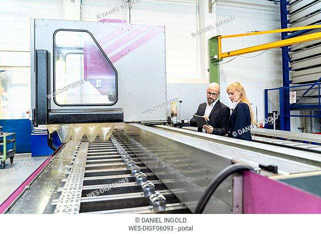 Businessman and businesswoman with tablet at conveyor belt in factory