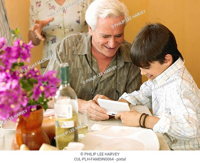 Boy 8-10 and grandfather playing portable video game at dining table