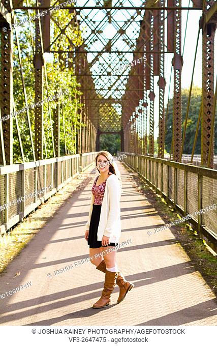 Teen girl poses for a high school senior portrait photo outdoors near a river in Eugene Oregon