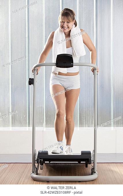 Smiling woman using exercise machine