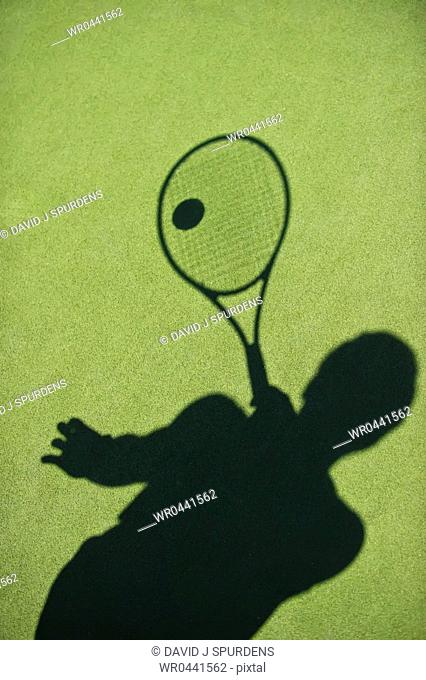 The shadow of a tennis player cast on the court