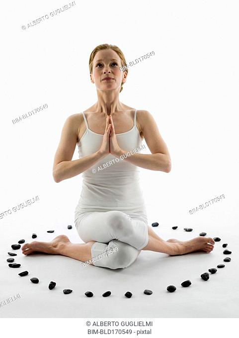Caucasian woman meditating in ring of stones