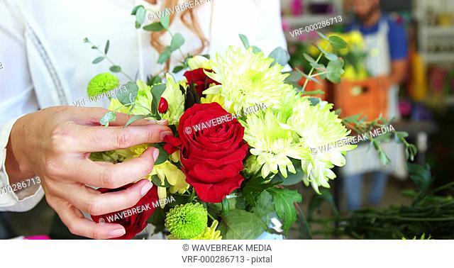 Female florist arraigning flower in flower vase