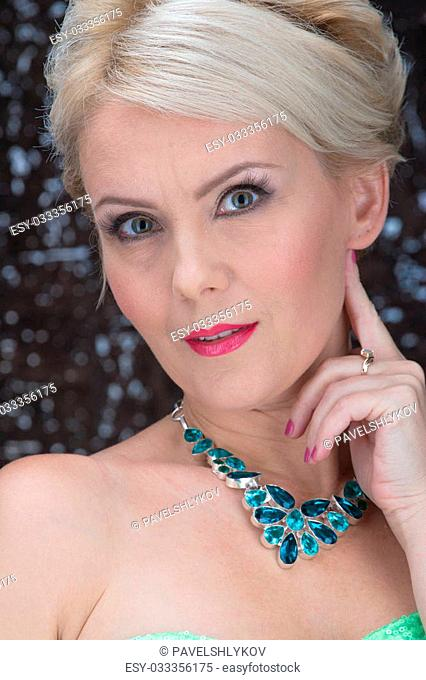Closeup portrait of adult woman beautiful face with perfect makeup and necklace