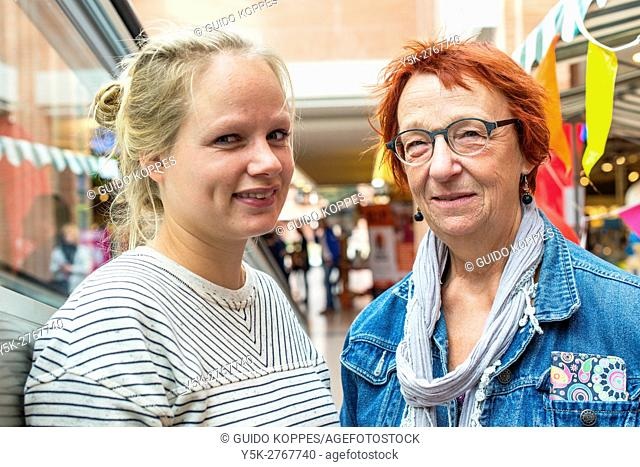 Rijen, Netherlands. Dual Portrait of a young adult and senior adult woman hanging out in a shopping mall