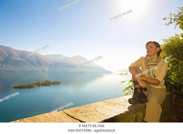Woman Relax and Enjoy the Panoramic View Over Alpine Lake Maggiore with Brissago Islands and mountain with Sunshine in Ticino, Switzerland