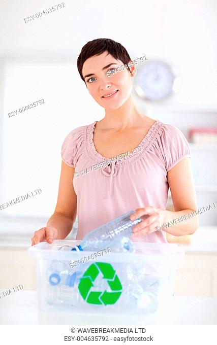Cute brunette Woman putting bottles in a recycling box