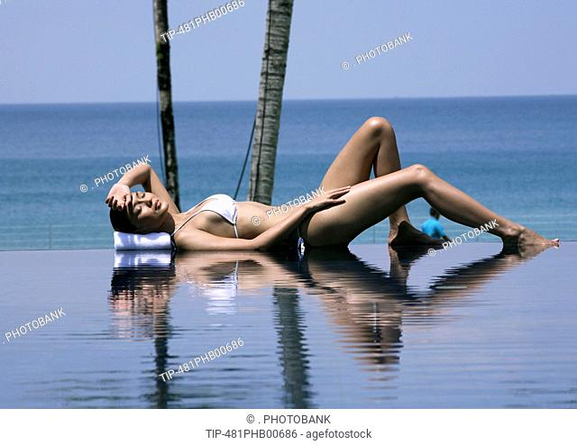 Woman lying on pool edge