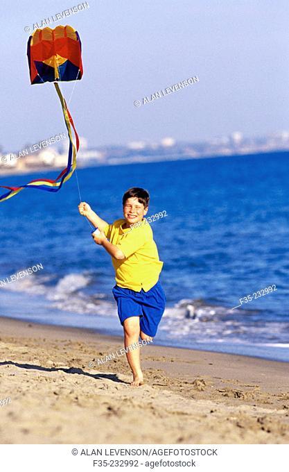 Happy boy running on beach with kite