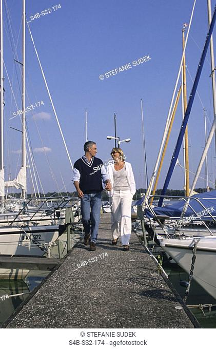 Middle-aged man and woman walking along a footbridge - Landing stage - sailing boats - leisure time - Togetherness - Trip
