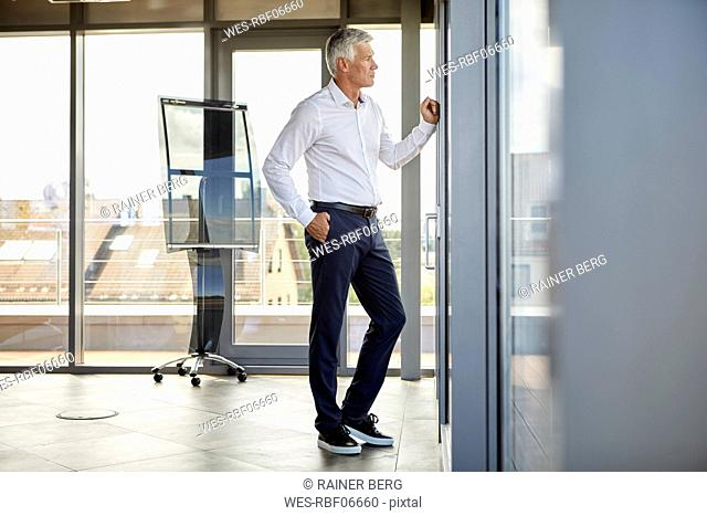 Worried businessman standing in office, looking out of window