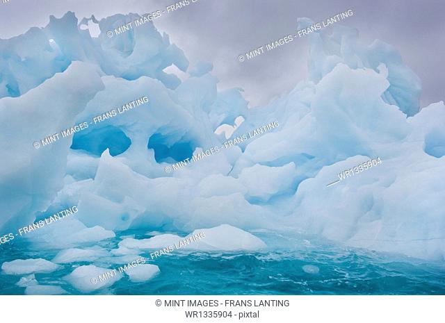 Melting icebergs with ice formations and shapes with holes, floating on the waters off the shores of East Greenland