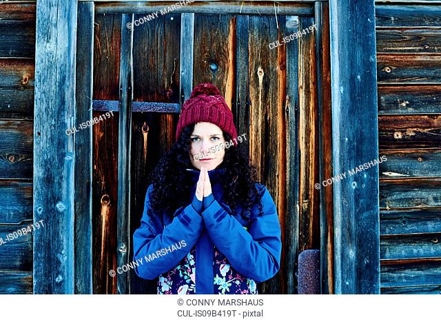Portrait of woman in knit hat practicing yoga, meditating by log cabin door