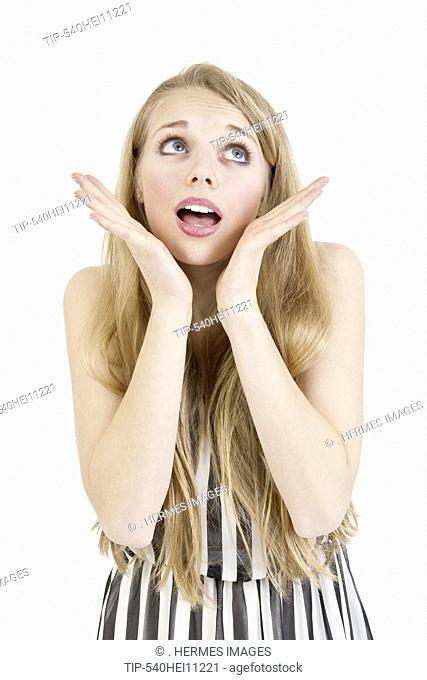 Happy young female looking in amazement over white background