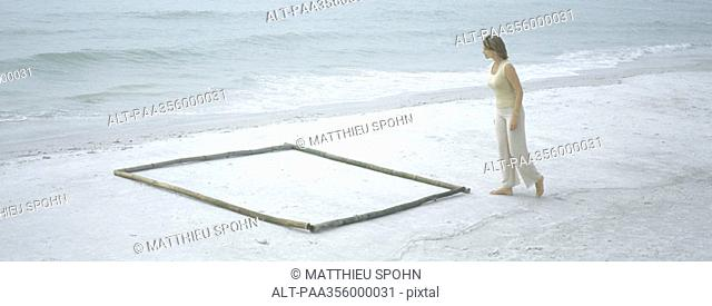 Woman approaching square shape on beach