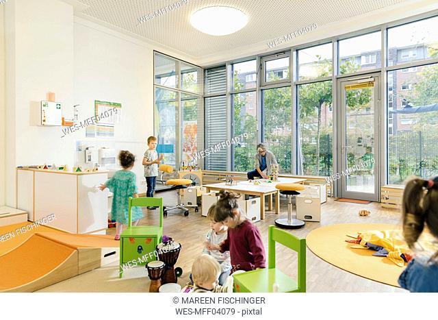 Pre-school teacher and children in playing in learning room in kindergarten