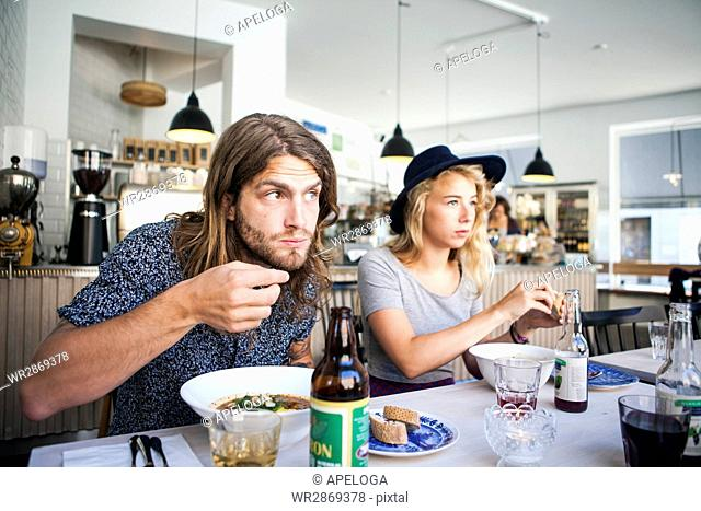 Young male and female friends having food at table in restaurant