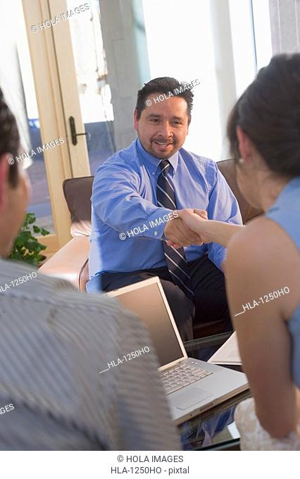 Rear view of a young woman shaking hands with a real estate agent