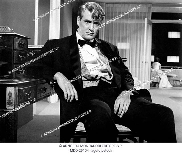 Rock Hudson in the film The Giant. American actor Rock Hudson (Roy Harold Fitzgerald) sitting and leaning on a piece of furniture in the film The Giant