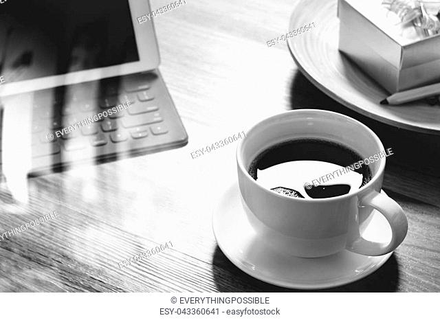 Coffee cup and Digital tablet dock smart keyboard,gold gift box and round wood tray,color pencil on wooden table,black and white