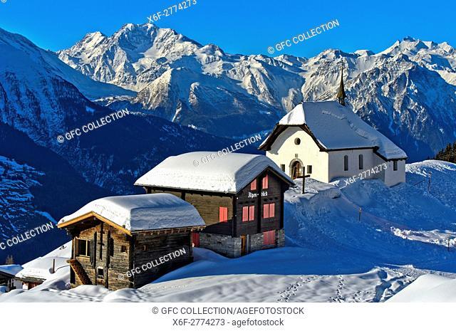 Snow-covered chapel Kapelle Maria zum Schnee against the peaks of the Pennine Alps, Bettmeralp, Valais, Switzerland