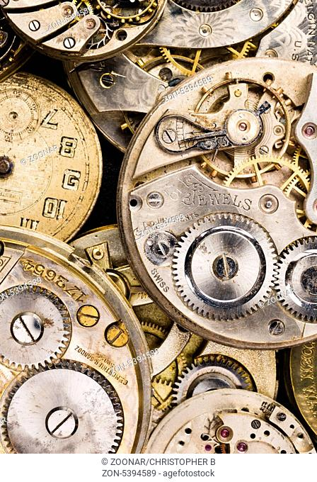 Vintage time pieces lay in a pile needing repair