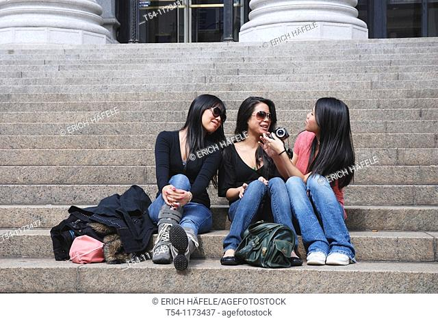 Three Asian woman sitting on the steps of New Yorks main post office and looking at photos