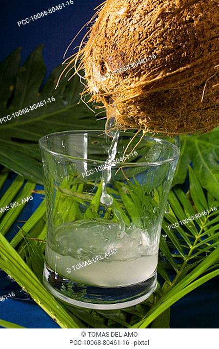 A coconut emptying it's juice into a cocktail glass