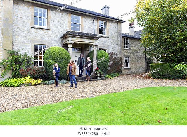 Caucasian family standing near house