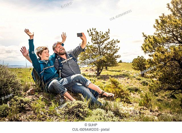 Father and teenage son waving for selfie on hiking trip, Cody, Wyoming, USA