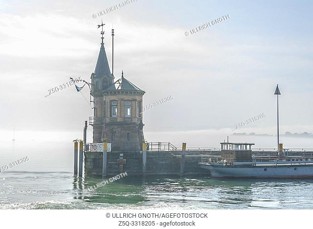 Konstanz, Baden-Wurttemberg, Germany, Europe: Mist from Lake Constance spreads all over the harbour and encloses the lighthouse