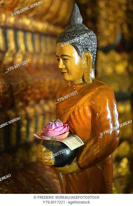 Marble Buddha statue carrying a banknote offering and a lotus flower, Wat Phnom temple, Phnom Penh, Cambodia, South East Asia, Asia