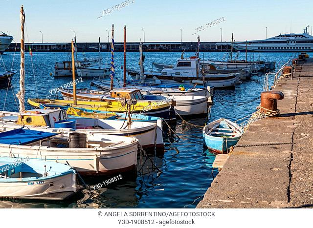 Line of little boats illuminated by sun at sunset, winter in Capri island, Bay of Naples, Italy