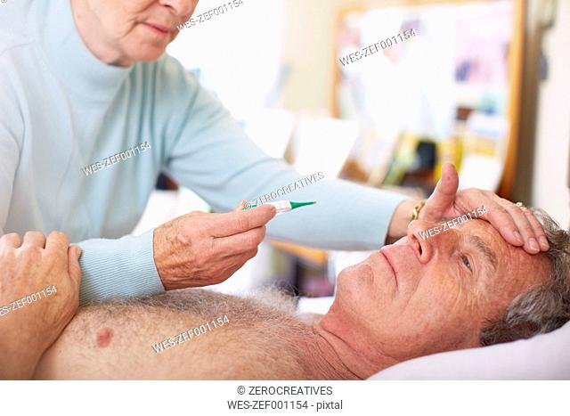 Senior woman taking temperature of sick husband at home